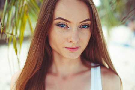 Portrait of beautiful young woman with long hair and palm leaves behind