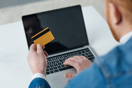 Man paying for online purchase with credit card and laptop Stok Fotoğraf