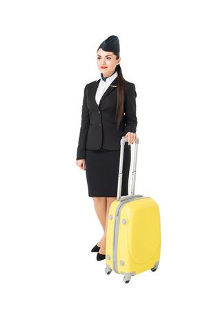 Young female stewardess leaning on suitcase isolated on white background