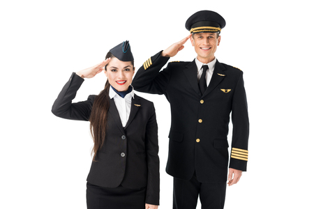 Young stewardess and pilot saluting isolated on white background
