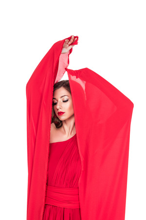 Glamorous girl posing in red dress with veil, isolated on white background Stock Photo