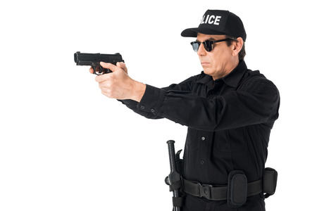 Serious policeman in sunglasses aiming gun isolated on white background