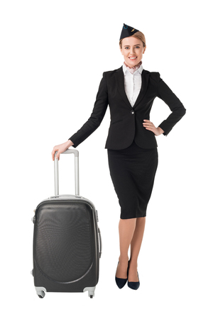 Young female stewardess leaning on suitcase isolated on white background