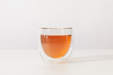 Close-up view of fresh hot tea in glass cup on grey background