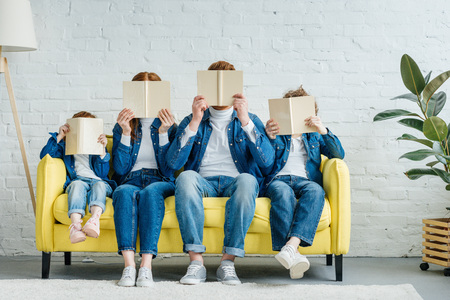 Family sitting on sofa and holding books in front of their faces