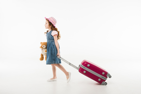 Little stylish tourist in hat with teddy bear and suitcase isolated on white background, travel concept