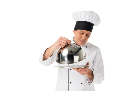 Man in chef uniform looking on tray with cover isolated on white background Stock Photo