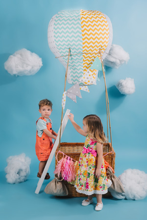 Beautiful little kids pretending to fly on hot air balloon in cloudy sky background 版權商用圖片