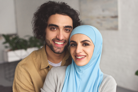 Porträt eines lächelnden muslimischen Paares, das zu Hause in die Kamera schaut