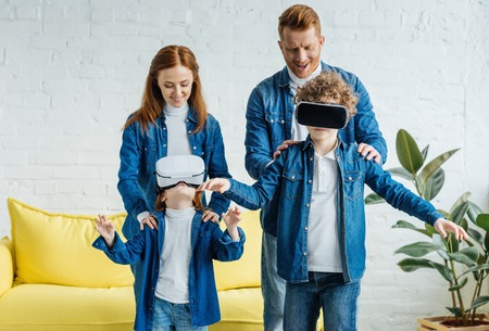 Children using vr glasses standing in front of their smiling parents Imagens