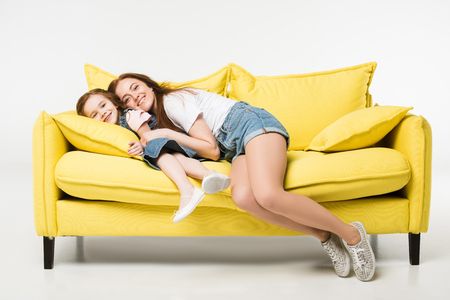 Happy mother and daughter on sofa isolated on white background