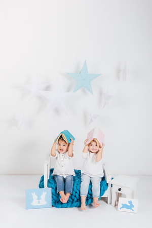 Adorable little kids sitting on blue knitted plaid and covering heads with books and rabbit cards, Easter concept Stock Photo