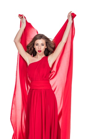 Glamorous woman in red posing with chiffon veil, isolated on white background