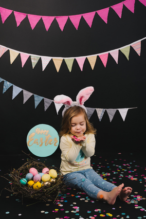 Cute little child with bunny ears and Easter eggs in nest blowing confetti on black background