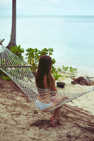 Back view of woman in bikini resting in hammock with ocean on background