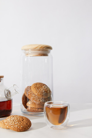Close-up view of tea in glass cup, delicious cookies and teapot on grey background