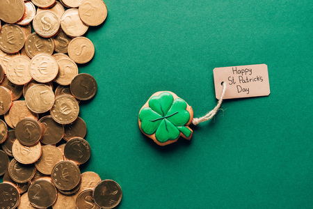 Top view of icing cookie in shape of shamrock and golden coins on green background, St Patricks day concept Stok Fotoğraf