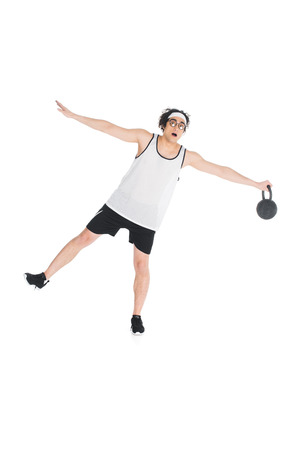 Young skinny sportsman in eyeglasses standing on one leg and holding kettle-bell isolated on white background Stock Photo