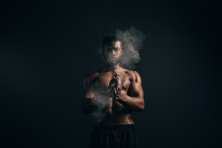 Young African American sportsman applying talcum to hands and looking at camera on black background