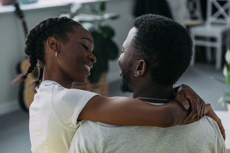 Back view of young African American couple embracing and smiling each other at home