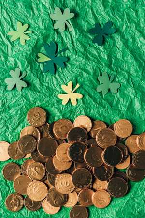 Top view of golden coins and paper shamrock on green surface background, St Patricks day concept Stok Fotoğraf