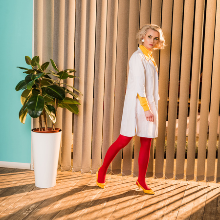 Beautiful retro styled doctor in colorful dress and white coat walking in clinic
