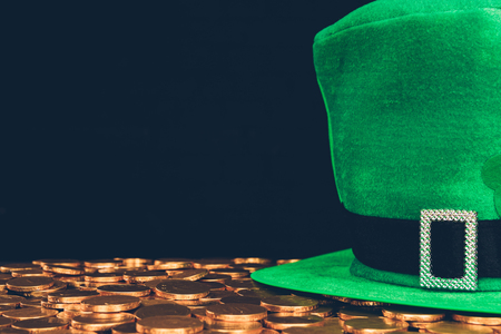 Green hat on golden coins isolated on black, St Patrick's day concept