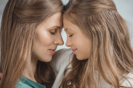 Side view of mother and daughter touching with foreheads at home Фото со стока