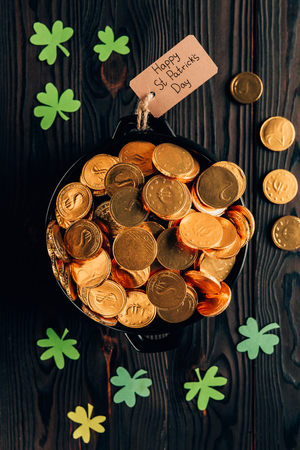 Top view of pot with golden coins and shamrock on wooden table, St Patricks day concept Stok Fotoğraf