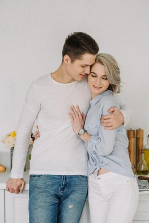 Handsome boyfriend hugging attractive girlfriend at kitchen