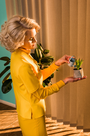 Side view of beautiful old-fashioned woman in yellow dress watering potted plant with small watering can at home