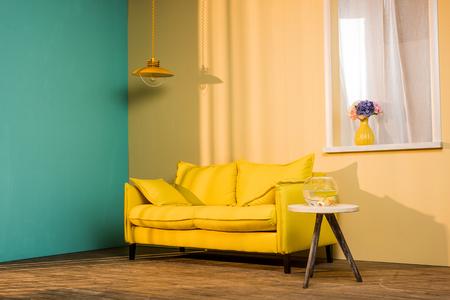Gele bank en aquarium op tafel in woonkamer