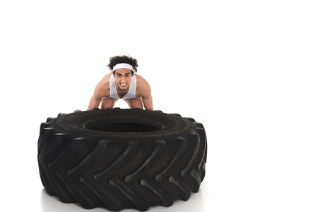 Young skinny sportsman raising big tyre of wheel isolated on white background 写真素材