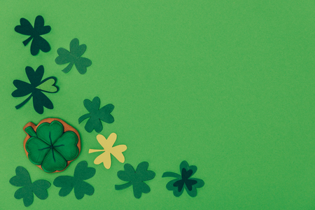 Top view of gingerbread in shape of shamrock and paper shamrock isolated on green background, St Patricks day concept