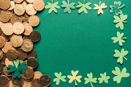 Top view of shamrock and golden coins on green background, St Patrick's day concept