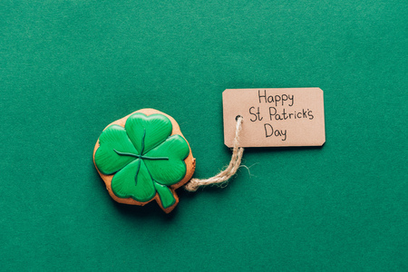 Top view of icing cookie in shape of shamrock on green background, St Patricks day concept