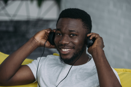 Handsome African American man listening music in headphones and smiling at camera