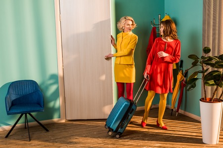 Beautiful old-fashioned girl meeting friend with travel bag at home Stock Photo