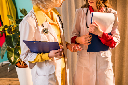 Cropped image of retro styled doctors in white coats talking in clinic Stock Photo