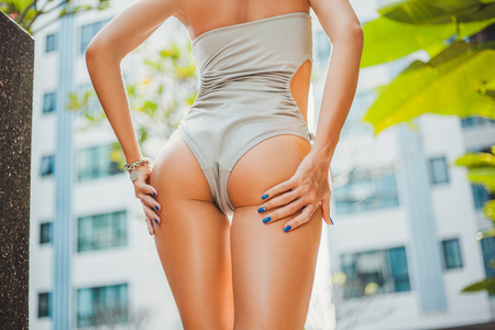 Cropped shot of attractive woman in grey swimsuit with hands on buttocks