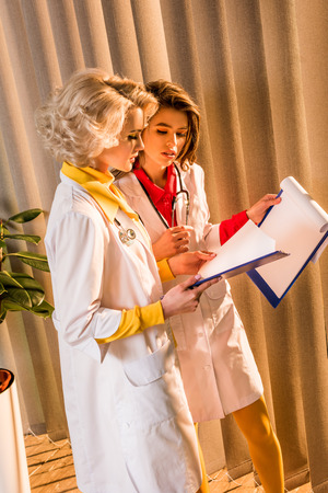Side view of beautiful retro styled doctors reading diagnosis in clipboard in clinic
