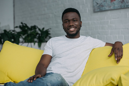 Portrait of handsome young African American man sitting on sofa and smiling at camera