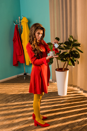 Beautiful old-fashioned woman in colorful dress watering potted plant with small watering can at home Banque d'images - 111742997