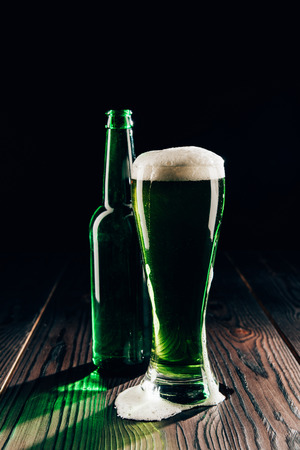 Glass and bottle of green beer on wooden table, St Patricks day concept