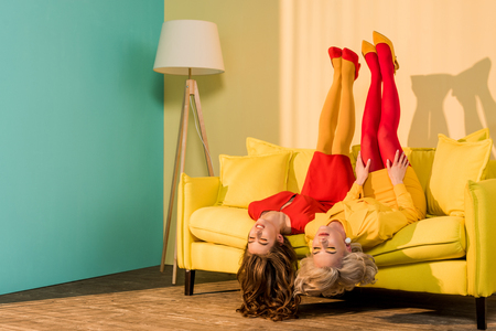 Retro styled attractive girls in colorful dresses lying upside down on sofa at home 免版税图像