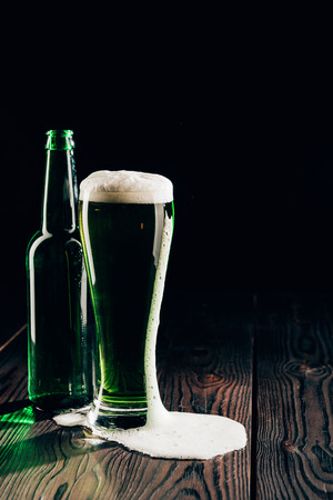 Glass and bottle of green beer on wooden surface, St Patricks day concept