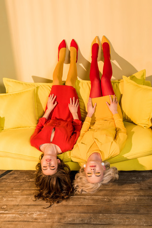 Retro styled beautiful girls in colorful dresses lying upside down on sofa at home