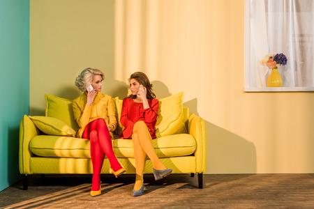 Retro styled women talking on smartphones on yellow sofa, doll house concept Standard-Bild