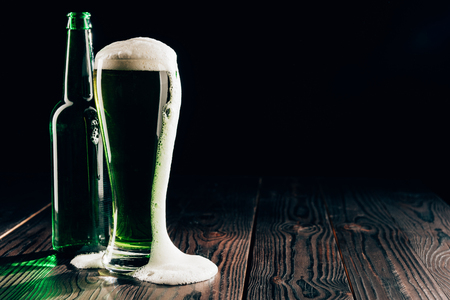 Glass and bottle of green beer with foam on table, St Patricks day concept