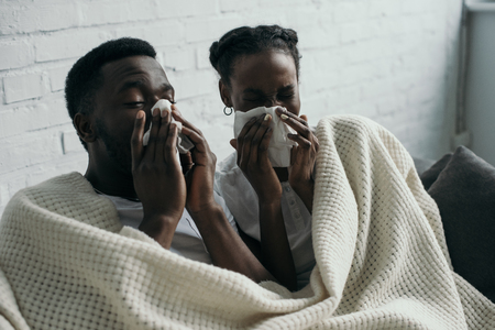 Young African American couple holding paper napkins while having flu together at home Stock Photo